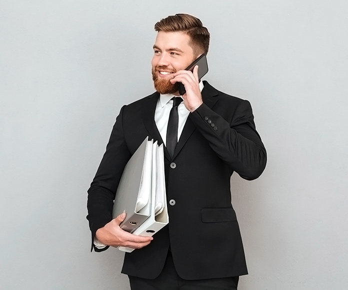 hombre con traja hablando por teléfono y sujetando unos archivadores de documentos