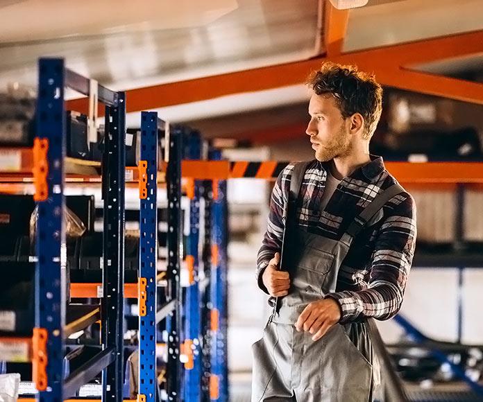 hombre montando unas estanterías industriales