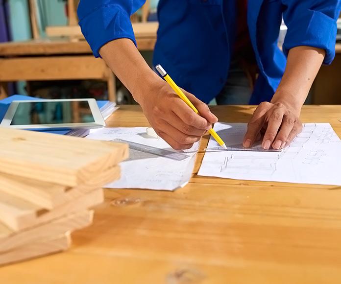 hombre midiendo y cortando maderas