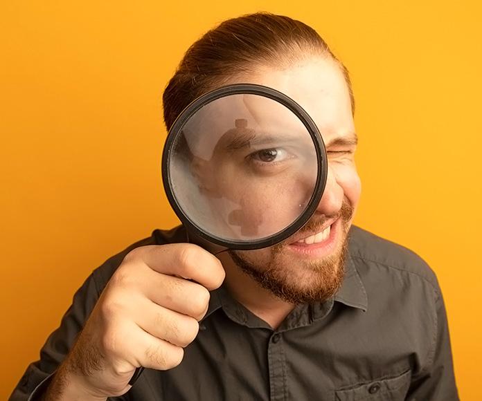 hombre joven mirando a través de una lupa