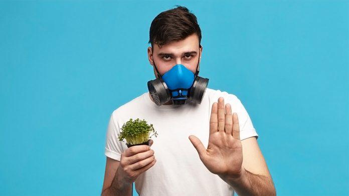 hombre con máscara de gas sujetando una planta