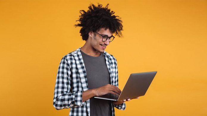 joven sujetando un ordenador portátil