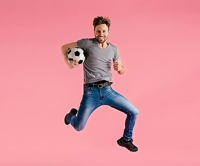 hombre saltando con un balón de fútbol bajo el brazo