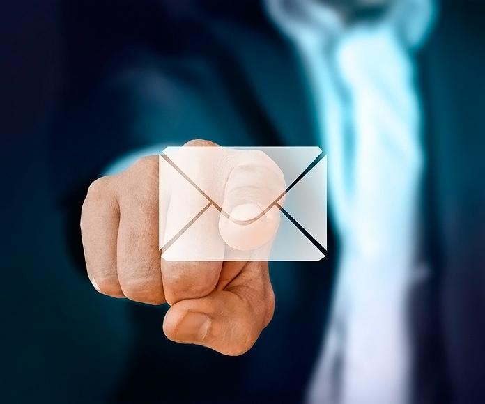 Hombre trajeado pulsando un icono de email iluminado
