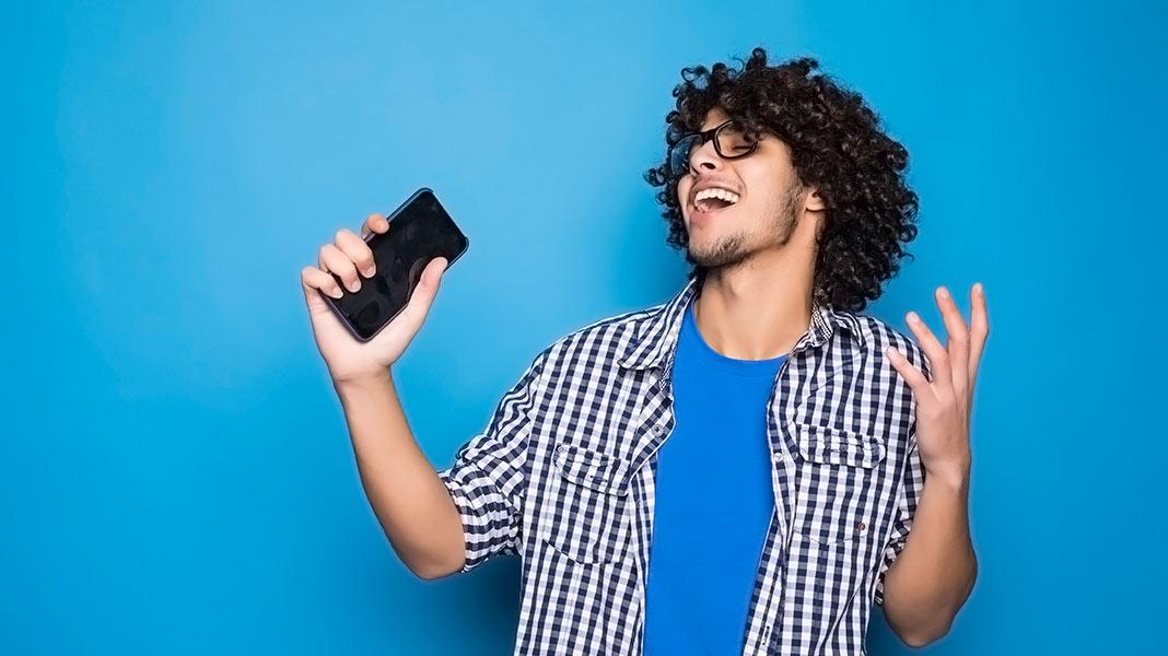 chico feliz sujetando un teléfono móvil