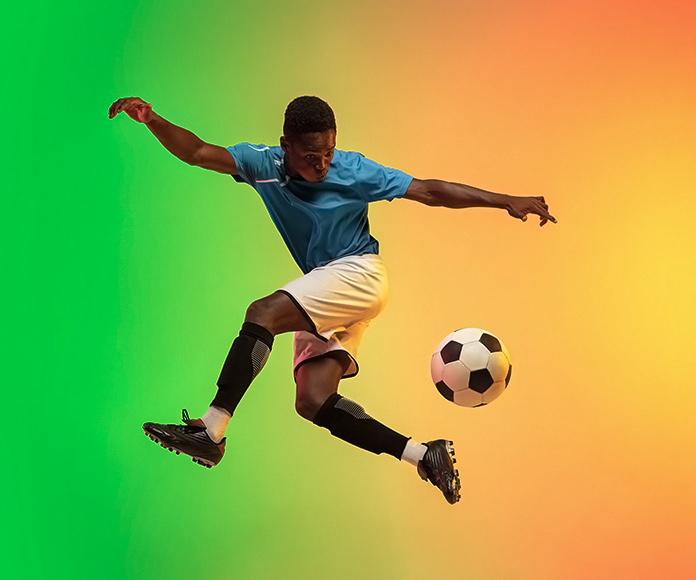 jugador de fútbol golpeando el balón con el talón en el aire