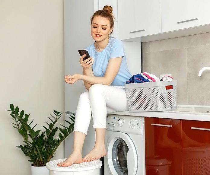 chica sentada sobre la lavadora mirando el teléfono