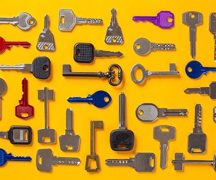 Muchas llaves de diferentes tipos ordenadas sobre un fondo amarillo