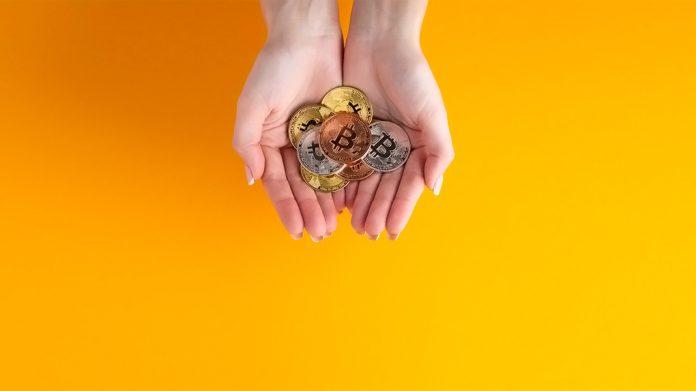 manos sujetando bitcoins
