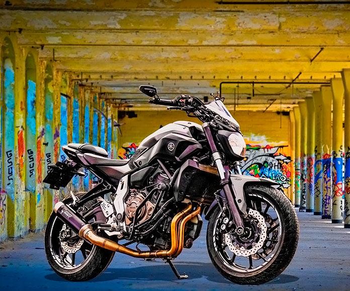 motocicleta aparcada en unos soportales llenos de graffitis