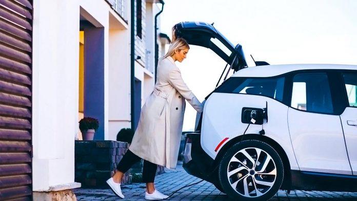 mujer cargando un vehículo eléctrico