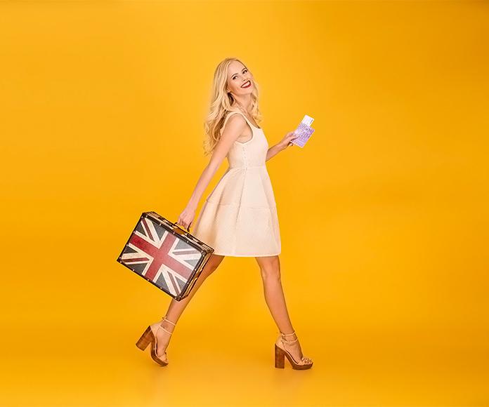 mujer caminando con una maleta que tiene la bandera de Inglaterra