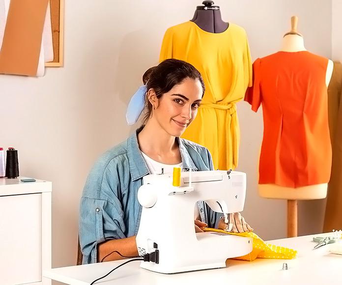 mujer sonriendo mientras usa una máquina de coser