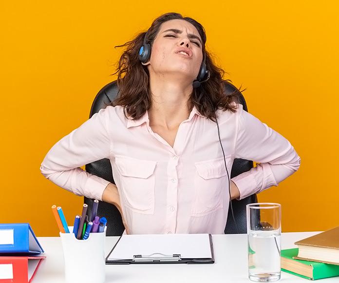 mujer en una oficina tocándose la espalda con cara de dolor