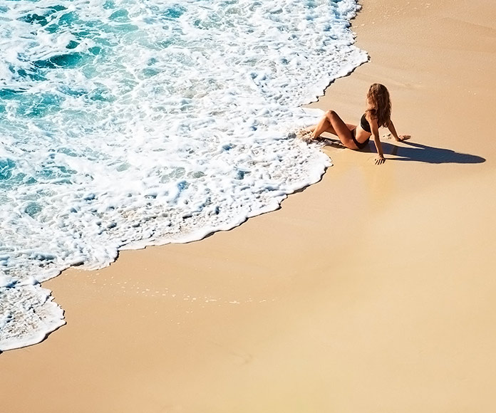 mujer mojándose los pies en la orilla de una playa