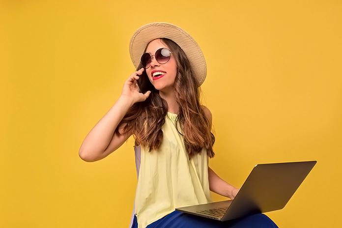 Mujer trabajando en un ordenador portátil mientras toma el sol