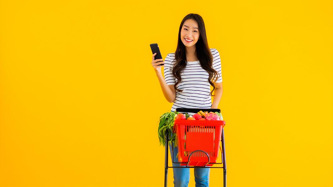 chica llevando un carrito de supermercado lleno de comida con un móvil en la mano