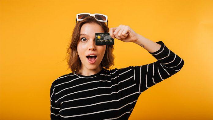 Chica tapándose un ojo con una tarjeta de crédito