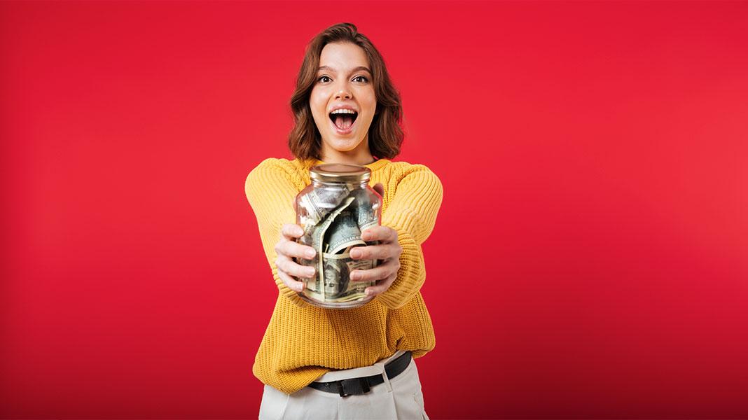 mujer feliz sujetando un tarro lleno de dinero