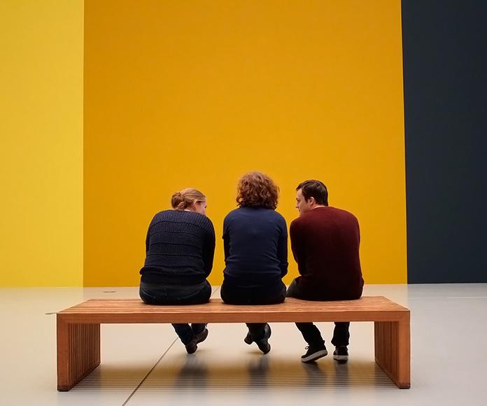 visitantes de un museo sentados frente a una obra