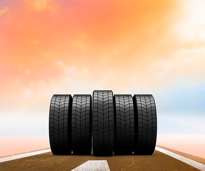 5 neumáticos en la carretera con una puesta de sol de fondo