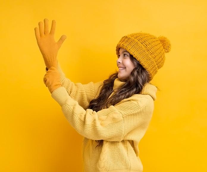 niña vestida con abrigo y gorro de invierno poniéndose unos guantes