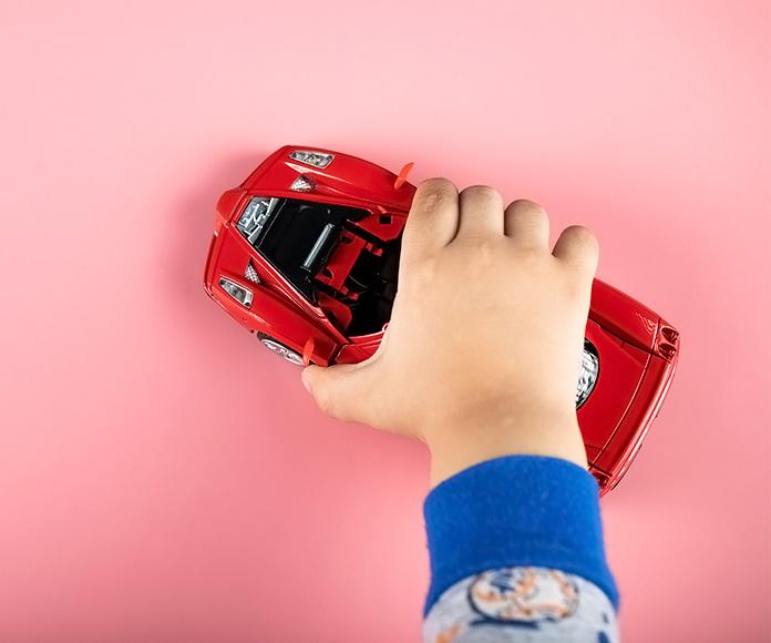 mano de niño jugando con un coche rojo de juguete
