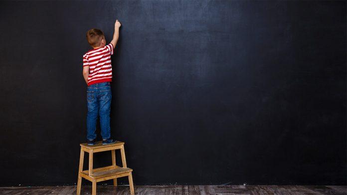 niño subido a una escalera escribiendo en una pizarra