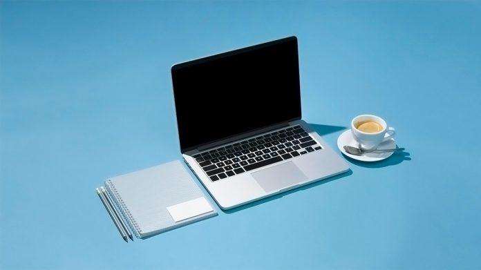 ordenador portáil, libreta, lápices y una taza de café sobre un fondo azul