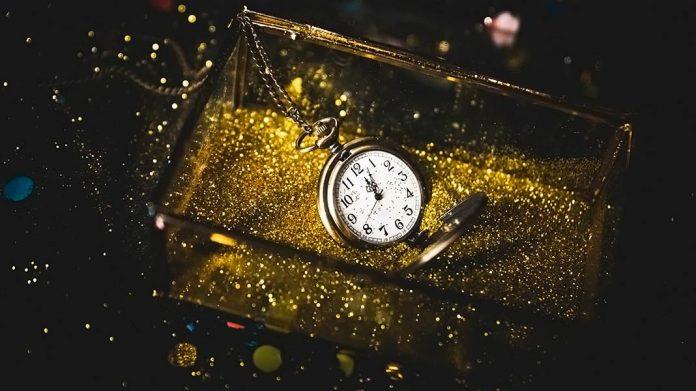 reloj de oro cayendo dentro de una caja con lentejuelas doradas