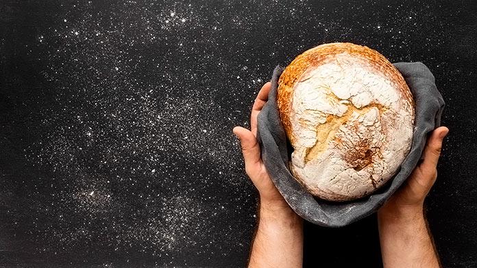 manos enseñando un pan artesano sobre un paño negro