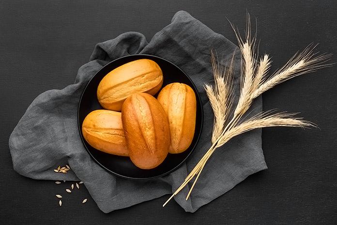 panecillos en un plato negro sobre una servilleta negra y junto a unas espigas de trigo