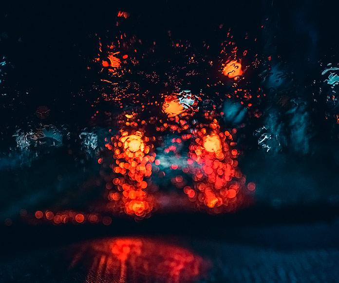 visión borrosa a través del parabrisas del coche una noche lluviosa