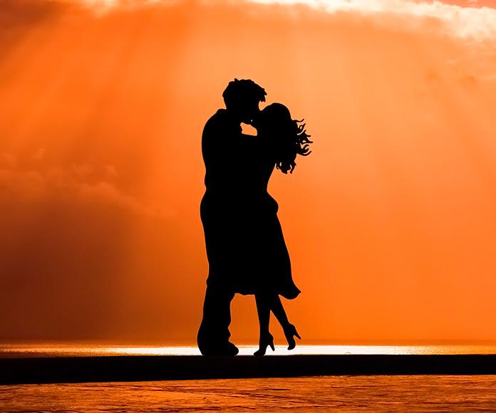 sombra de una pareja besándose en la playa al atardecer