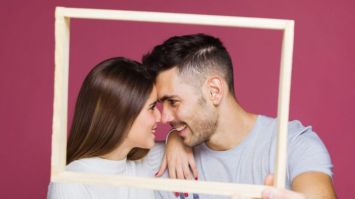 pareja feliz sujetando un marco
