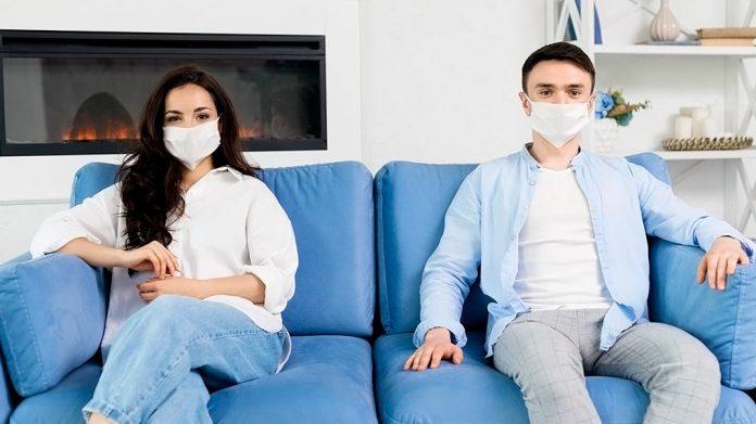 pareja con mascarillas sentada separada en un sofá