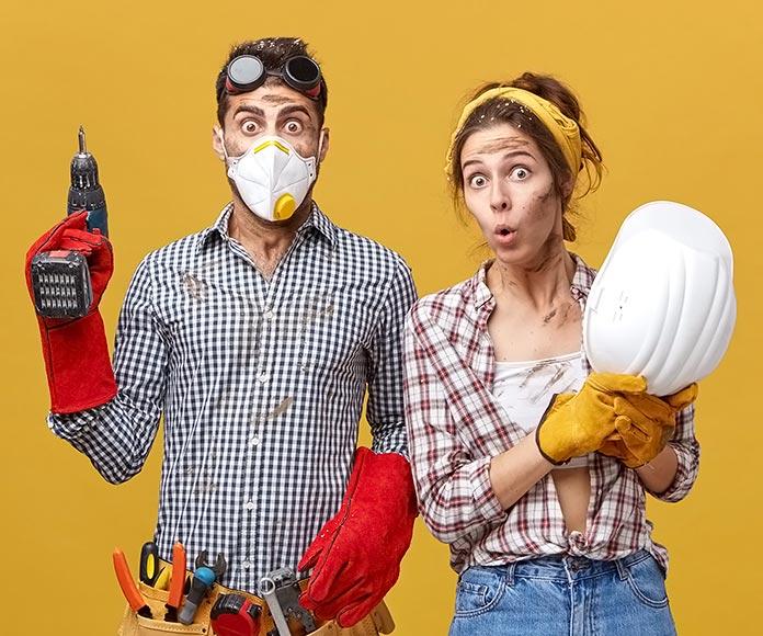 pareja vestidos como obreros con herramientas de construcción