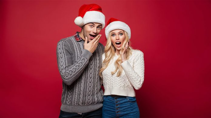 pareja con gorros de Navidad y cara de sorprendidos