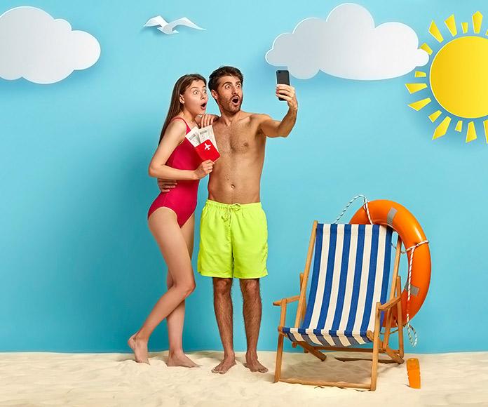 pareja haciéndose un selfie en un decorado que simula la playa