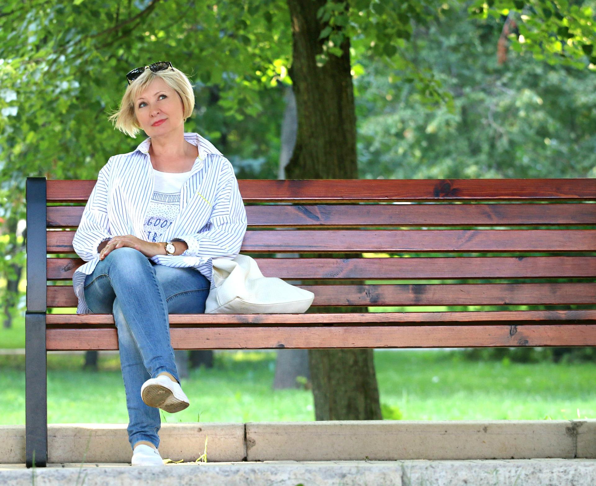 Mujer sentada en un banco pensado