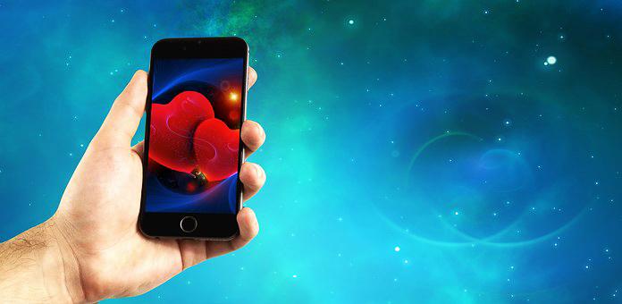 Hombre sujetando un teléfono móvil con la mano (Pixabay)