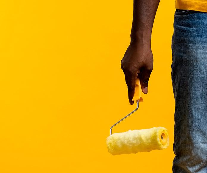 pintor pintando una fachada de amarillo