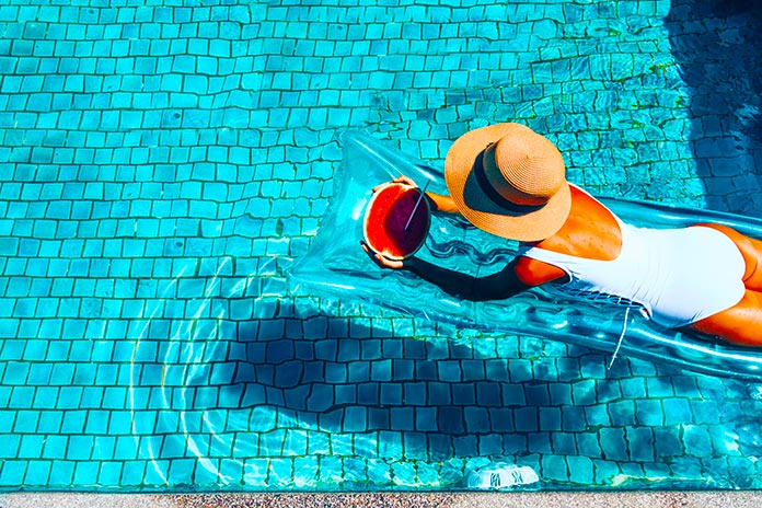 Mujer relajada comiendo sandía en una piscina