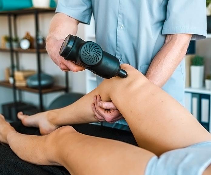 fisioterapeuta usando una pistola de masaje con un paciente