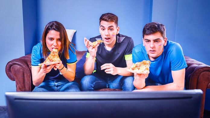 amigos viendo la televisión mientras comen pizza
