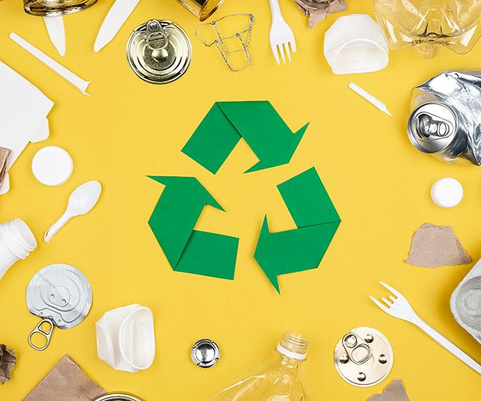 plásticos y envases rodeando el símbolo de reciclaje sobre un fondo amarillo