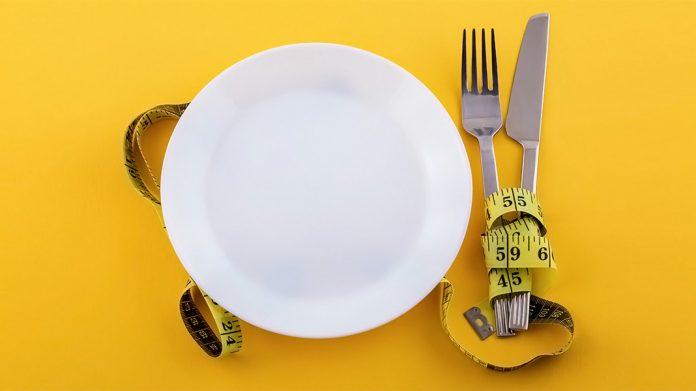 plato y cubiertos rodeados con una cinta métrica