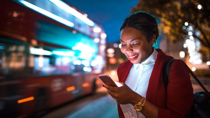 chica sonriendo mirando la pantalla de un teléfono móvil