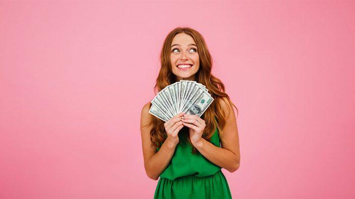 chica con un abanico de billetes en la mano