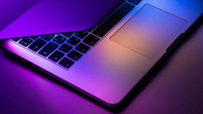 ordenador Apple MacBook iluminado en la oscuridad